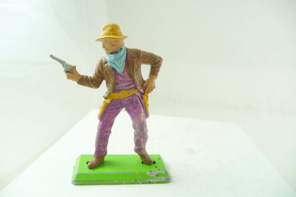 Britains Deetail Cowboy standing, firing with pistol at side, brown jacket, purple pants