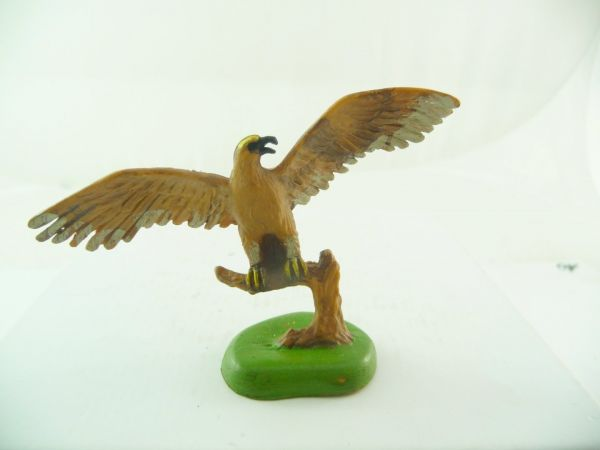 Britains Eagle with spread wings sitting on branch, light-brown